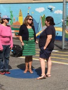 Principal Linore Lindy (middle in blue and green dress) comforts nervous parents while they wait for their kids after the first day of school. Will their child be ok? Of course!